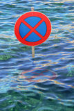 Overflowed street with traffic sign in the waves Stock Photo