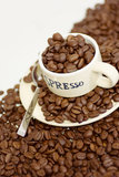 Overflowing with beans. Espresso cup overflowing with coffee beans Royalty Free Stock Photo