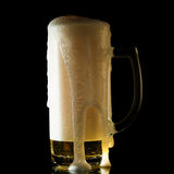 Overflowing beer mug Stock Photography