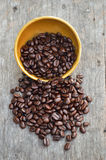 Overflowing bowl of coffee beans. Bowl with coffee beans, on wood background Royalty Free Stock Photos