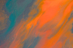 Overflowing bright orange and dark blue paint on paper Stock Images