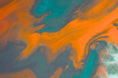 Overflowing bright orange and dark blue paint on paper Stock Photos