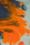 Overflowing bright orange and dark blue paint on paper. Shabby style abstract faded background. Mixing paints close-up. Abstract base backdrop abstract Stock Image