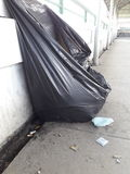 Overflowing garbage bag. On sidewalk Stock Photography