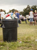 Overflowing garbage bin. England , Staffordshire - July 28 2013: A black bin-full of trash in an open field at the Staffordshire county show Royalty Free Stock Images