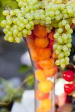 Grapes in a vase. Outside image of grapes overflowing out of a glass vase with oranges inside the vase stock photography