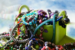 Overflowing jewelry. Green colored jewelry box over-packed with various bijou items Royalty Free Stock Image