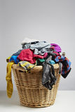 Overflowing laundry basket. Household chore concept on white background stock photo