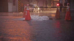 Overflowing manhole in storm with warning beacons. Slow motion stock video footage