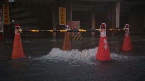 Overflowing manhole in storm with warning beacons. Slow motion stock footage
