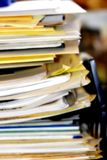 Overflowing Paperwork Inbox. Pile of business or healthcare paperwork and/or forms stacked in an overflowing inbox (shallow focus, soft focus royalty free stock images