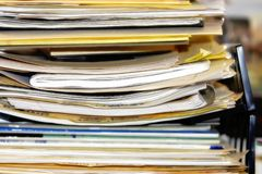 Overflowing Paperwork Pile #2. Pile of business or healthcare paperwork and/or forms stacked in an overflowing inbox (shallow focus, soft focus stock photography
