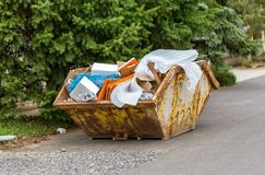 Overflowing rusty metal container for construction waste with cardboard boxes and plastic trash royalty free stock photos