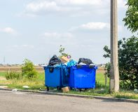 Overflowing waste cans with garbage bags, cardboard boxes and other garbage near the road. One waste can is broken royalty free stock photography