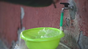 Overflowing water. Old tap on a crumbling wall fills a plastic basin, the water overflows and a man closes the valve stock footage