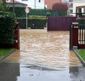 Overflown River and the road completely flooded while the mud go. Es in the courtyards of the houses royalty free stock photo