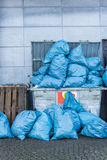 Overfull dumpster. Dumpster filled with blue garbage bags Stock Photography
