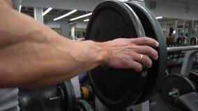 Overgangsschot van de bepaalde spiermens die zware platen op barbell zetten en in gymnastiek opheffen stock videobeelden