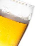 Overgeheld glas bier en dalingen op witte achtergrond royalty-vrije stock foto