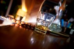 Overgeheld glas whisky op de bar met een waterpijp op een vage achtergrond stock fotografie