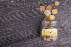 Overgehelde glaskruik met verspreide euro muntstukken met de inschrijvingsreis op een zwarte houten lijst