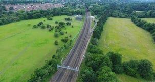 Overground railway line passing through green countryside stock video