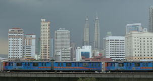 Overground train in Kuala Lumpur, Malaysia. Kuala Lumpur panorama with high-rise architecture and Petronas Twin Towers, Malaysia. Overground train passing by in stock video