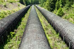 Overground Water Pipes at a Hydroelectric Power Station. Old Water Pipelines to a Hydroelectric Power Station on a Sunny Summer Day. Campbell River, BC, Canada Stock Photos
