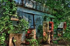 Overgrown Abandoned Garage with Derelict Gas Pumps Stock Photo