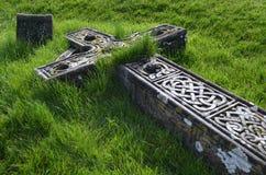 Overgrown Cross Ruins. Grass over growing a fallen cemetery cross in Ireland Stock Image