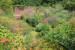 Overgrown decorative pond in the garden surrounded by flowering plants Stock Photo