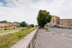Overgrown embankment of Parma river and city houses in cloudy summer day in Parma. Royalty Free Stock Image
