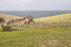 Overgrown Farm & Equipment. An old an rusted piece of farming equipment, resting in an overgrown field with the ocean, green grassy hills, and a blue sky Royalty Free Stock Photos