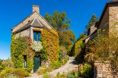 Overgrown houses in the village of Saint-Céneri-le-Gérei Normandy France royalty free stock photo