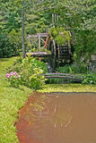 Overgrown Mill & Bridge. A muddy pond in front of an old gristmill obscured by undergrowth and trees Royalty Free Stock Photos