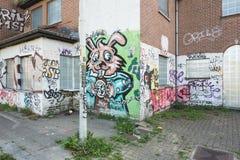 Overgrown sidewalk and graffiti Stock Images