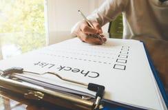 overhandig holdingspen op het document van de controlelijst en het formaat voor het invullen van informatie in bedrijfsconcept Royalty-vrije Stock Foto's
