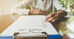 overhandig holdingspen op het document van de controlelijst en het formaat voor het invullen van informatie in bedrijfsconcept Stock Fotografie