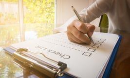 overhandig holdingspen op het document van de controlelijst en het formaat voor het invullen van informatie in bedrijfsconcept Stock Foto's