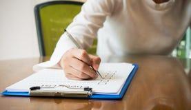 overhandig holdingspen op het document van de controlelijst en het formaat voor het invullen van informatie in bedrijfsconcept Royalty-vrije Stock Afbeelding