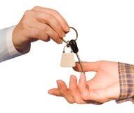 Overhandigend de sleutels die op witte achtergrond worden geïsoleerdl Stock Foto