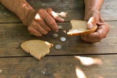 Overhandigt de slechte oude man ` s, stuk van brood en verandering, pence op houten achtergrond royalty-vrije stock foto