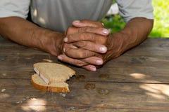 Overhandigt de slechte oude man ` s, stuk van brood en verandering, pence op houten achtergrond Het concept honger of armoede stock foto