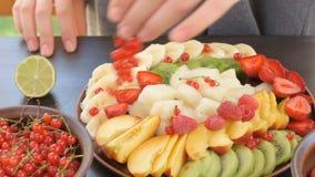 Overhandigt dienende fruit en bessenplaat stock video