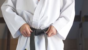 Overhandigt het aanhalen zwart band op de mens gekleed in kimono stock videobeelden