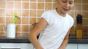 Overhandigt het close-up jonge meisje het kneden deeg op donkere lijst in keuken stock video