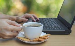 Overhandigt het drinken koffie en het gebruiken van laptop en bokeh achtergrond Stock Foto