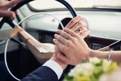 Overhandigt het jonggehuwde op een retro autowiel royalty-vrije stock afbeelding