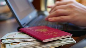Overhandigt het typen tekst op laptop, close-up van geld en paspoorten stock footage