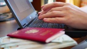 Overhandigt het typen tekst op laptop, close-up van geld en paspoorten stock video